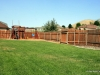 Fenced backyard with curbing, playset, shed, patio