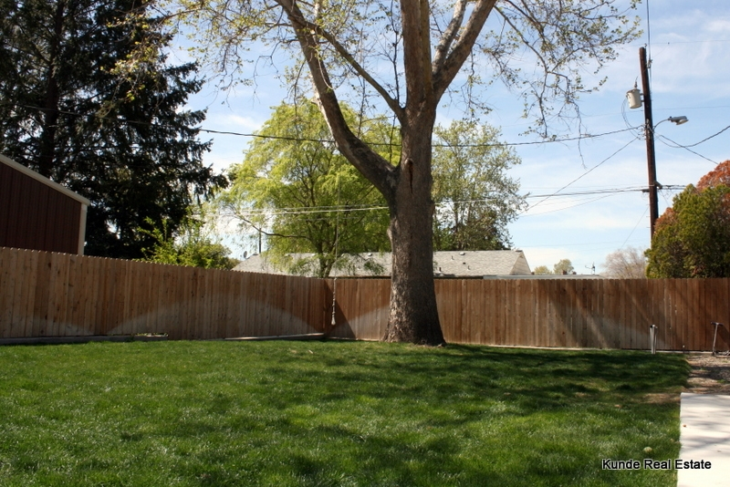 Backyard fully fenced and landscaped with storage shed and large patio/driveway/basketball court