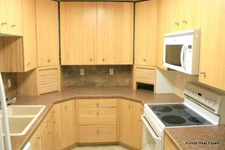 Kitchen includes dishwasher, range, microwave, refrigerator.