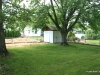 Backyard grassy area with 2 storage sheds